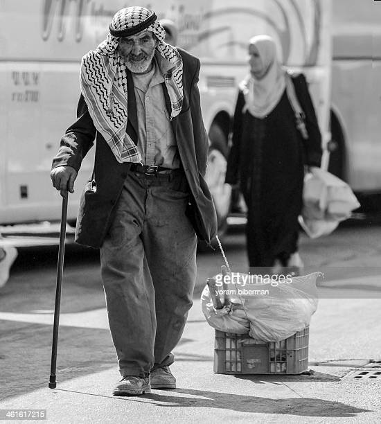 CONTENT] An old poor Palestinian man with a kafia and a walking stick walking pulling a box with his stuff A woman is seen behind him A bw photo