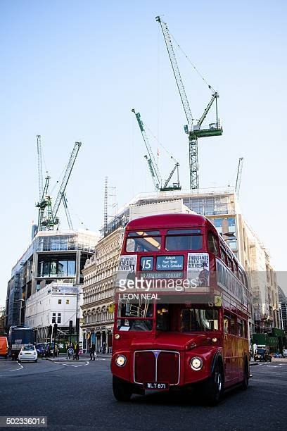 An old red London bus passes construction work continuing on buildings in the financial district in central London on December 23 2015 Britain's...