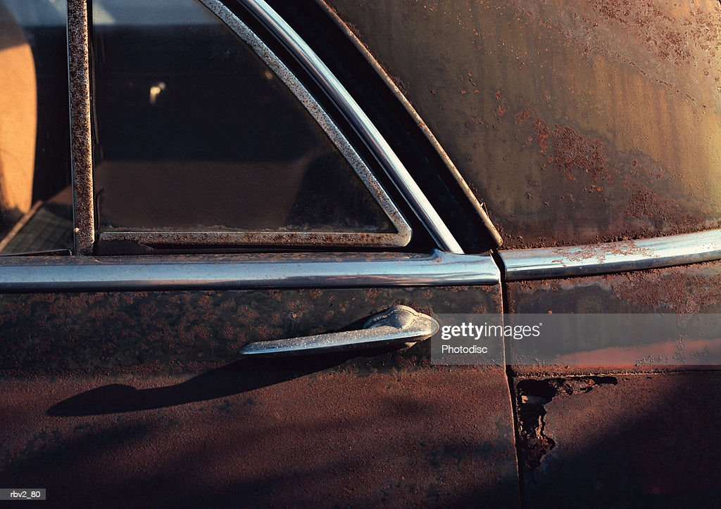 an old rusted car door holds a handle and stickers : Foto de stock