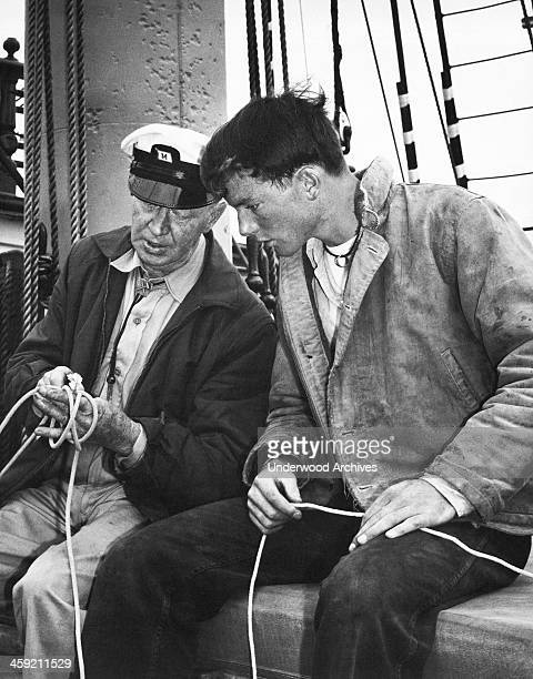 An old sailor gives a young man lessons in tying knots San Francisco California circa 1962