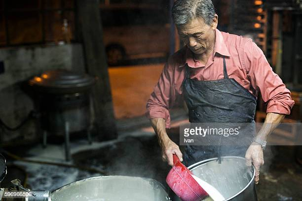 An Old Senior Asian Man Making Soy Milk and Tofu