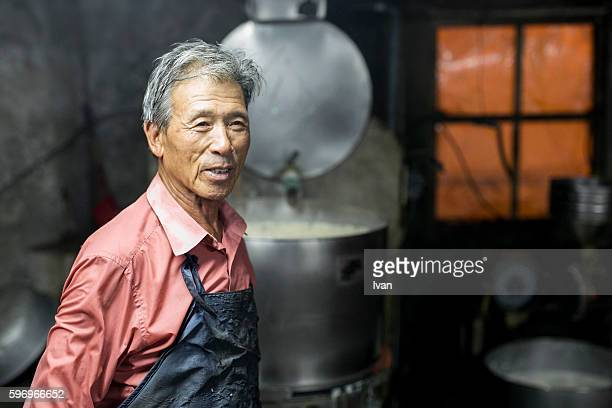 An Old Senior Asian Man Making Tofu and Soy Milk