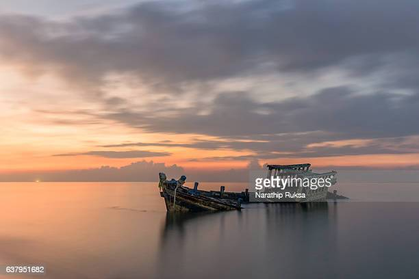 an old shipwreck or abandoned shipwreck taken during a beautiful sunset , wrecked boat abandoned stand on beach or shipwrecked off the coast of thailand. - sunken stock pictures, royalty-free photos & images