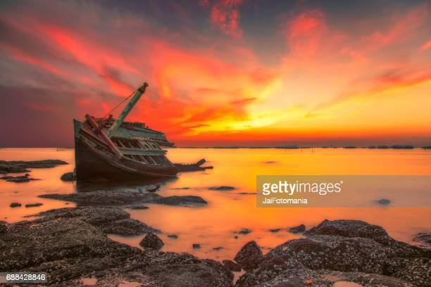 an old shipwreck or abandoned shipwreck.,boat capsized on a rocky beach in beautiful sunset background - 試合 セット ストックフォトと画像