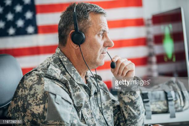 an old soldier sitting in an office uses a headset and a microphone - armed forces day stock pictures, royalty-free photos & images