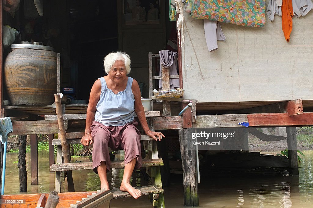 An Old Thai Woman Sits On The Wooden Stairs Of Her Home