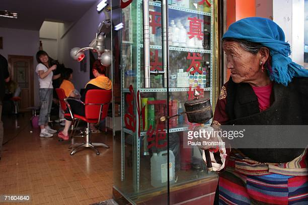 An old Tibetan woman peers into a hair salon August 5 2006 in a new section of Lhasa in the Tibet Autonomous Region China Lhasa's face is ever...