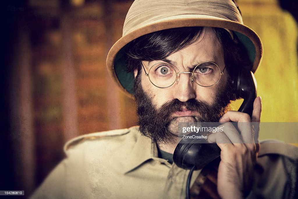An old time explorer or adventurer and a telephone : Stock Photo