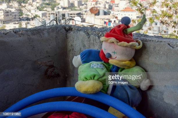 An old toy seen on the balcony of a Palestinian home in the West Bank with the Dheisheh Refugee Camp visible in the background