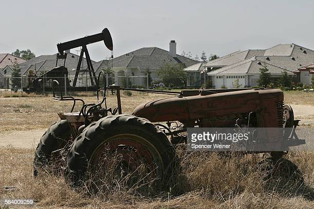 An old tractor and a still pumping oil well sit right across the street from recently completed homes in Bakersfield. Bakersfield is a city...