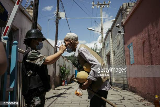 KUQA CHINA JUNE 29 2020 An old Uyghur is tested at a temperature checkpoint on June 29 2020 in Kuqa China