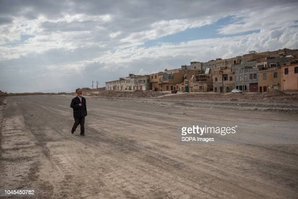 An old Uyghur man seen walking in a road under construction where it used to have traditional houses few month back like the ones in the background...