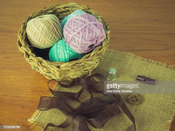 an old wicker basket with vintage style sewing tools - ribbon sewing item stock pictures, royalty-free photos & images