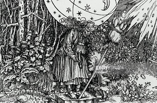 An old witch standing in a wooded area is holding a spindle in her right hand and an upright broom with several spindles in her left She is burdened...