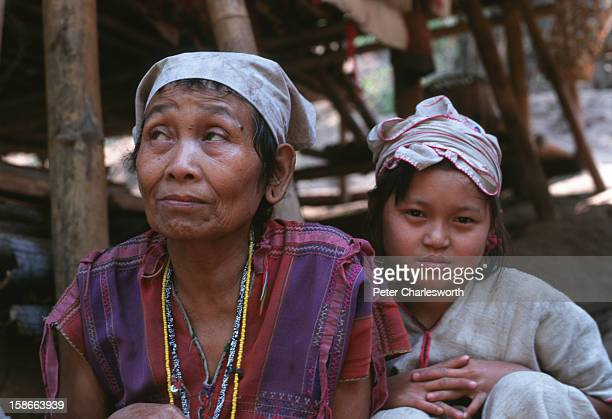 An old woman and a child squat on the floor under their wood and bamboo hut in a new Karen refugee camp north of the Thai town, Mae Sot. They are...
