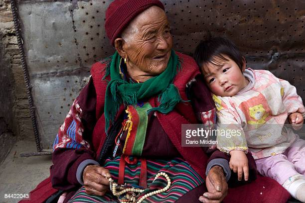 An old woman and her grandchild sitting on the side of the road from Shangri La to Yading a reserve in southwest Sichuan Province China This area of...