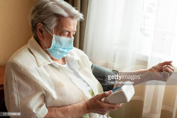 an old woman checking her blood pressure at home with a medical mask on her face. coronavirus prevention. quarantine - heart disease stock pictures, royalty-free photos & images