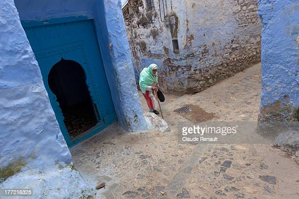 CONTENT] An old woman climbing up the stairs in Chefchouen