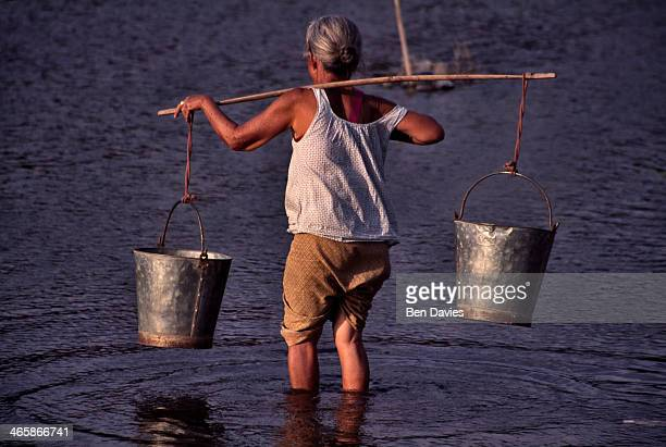 An old woman collects water from the Heuang River in Loei Province in Northeast Thailand In poorer parts of rural Thailand and especially the...