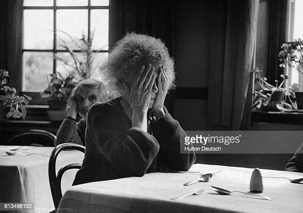 An old woman covers her face with her hands as she waits for dinner to be served in the dining room of a psychiatric hospital