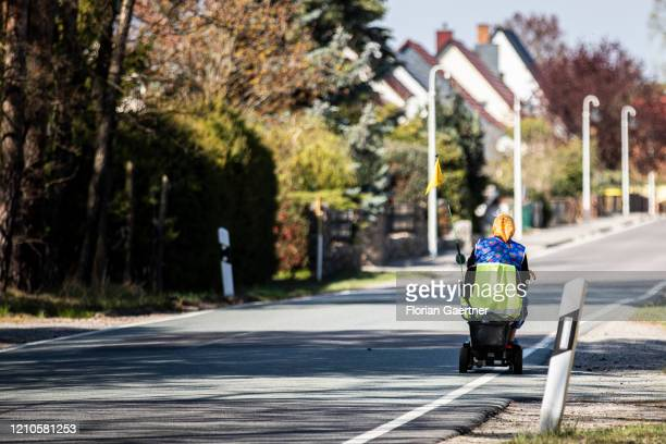 An old woman drives her electric vehicle through a village on April 21, 2020 in Kringelsdorf, Germany.