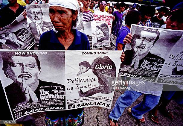 An old woman holds a poster demanding the resignation of Philippine President Joseph Estrada November 4 2000 during a massive rally in Mandaluyong...