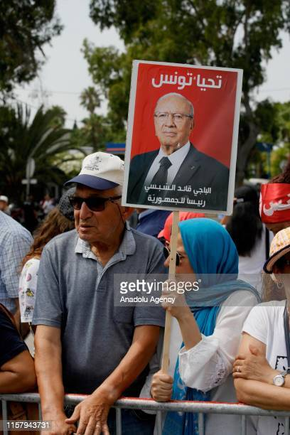 An old woman holds an image of the late Tunisian President Beji Caid Essebsi outside the Carthage Presidential Palace during his funeral in Tunis,...