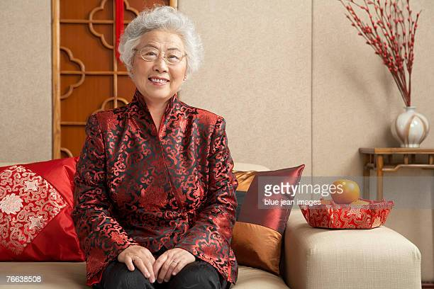 An old woman in Chinese traditional clothing sitting on the sofa celebrates Chinese New Year.