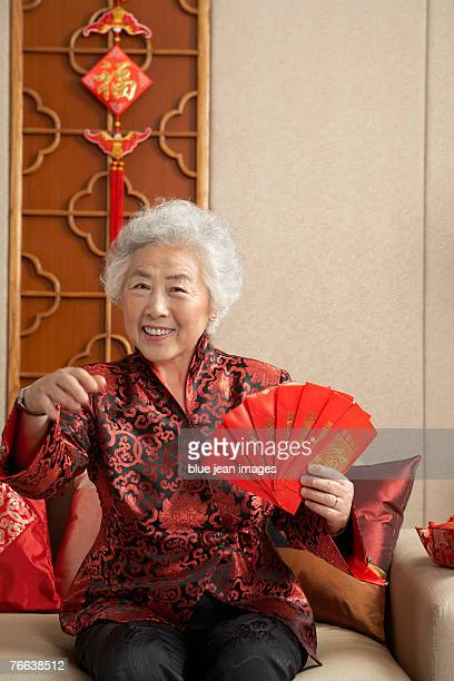 An old woman in Chinese traditional clothing with red envelopes sitting on the sofa celebrates Chinese New Year.