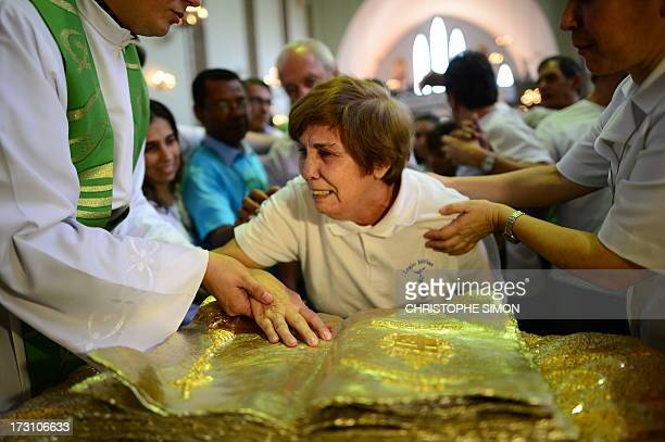 An old woman is assisted to touch a relic during a mass officiated by Cardinal Stanislaw Rylko to celebrate the arrival in Brazil of the relics of...