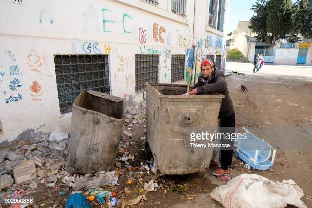 An old woman is reduced to scavenging for food in bins to survive on December 24 in El Kef Tunisia