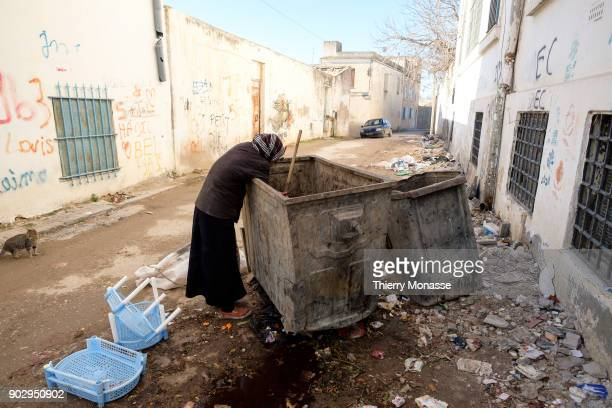 An old woman is reduced to scavenging for food in bins to survive on December 24 in El Kef, Tunisia.