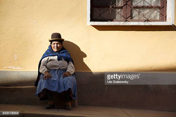 An old woman is sitting in front of a house in a small village in the Andes on April 14 2016 in Bolivar Bolivia