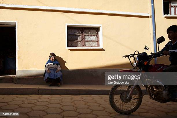 An old woman is sitting in front of a house in a small village in the Andes In the foreground a motorcycle passes on April 14 2016 in Bolivar Bolivia