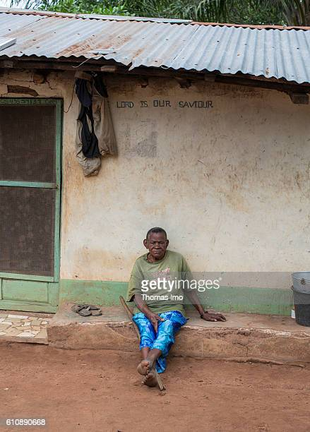 An old woman is sitting in front of her house on a cashew farm in Congo Above her the inscription Lord is our savior is written on the house on...