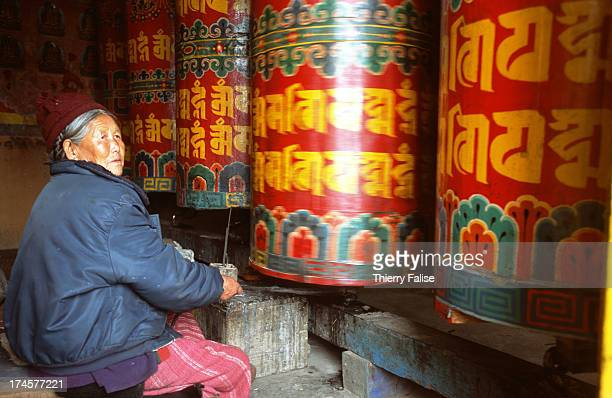 An old woman is turning the prayer wheel in the Tawang monastery