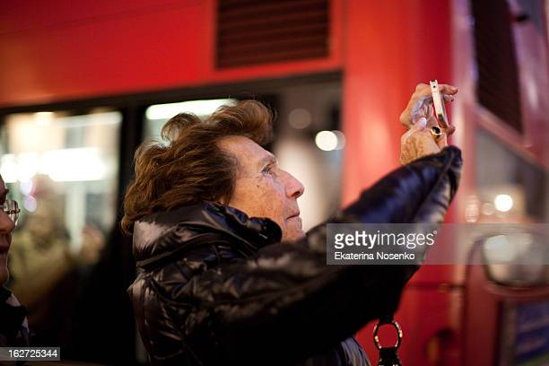 An old woman is using her smart phone to take pictures of the Christmas lights at Oxford Street. London, December 2012.