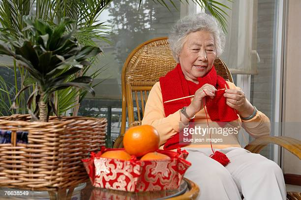 an old woman knitting in the chair celebrates chinese new year. - 63 year old female stock pictures, royalty-free photos & images