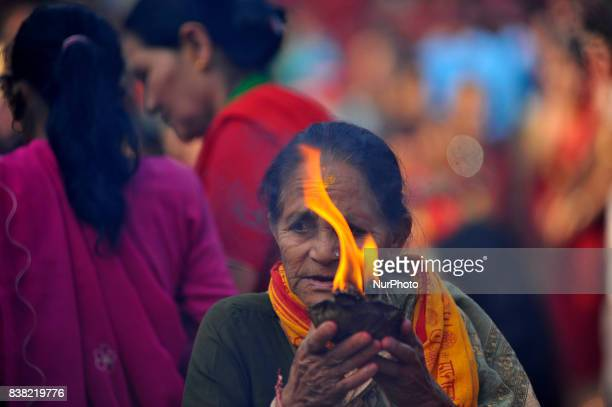 An old woman offering oil and butter lamps during Teej festival celebrations at Pashupatinath Temple Kathmandu Nepal on Thursday August 24 2017 The...