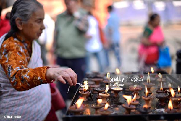 An old woman offering ritual prayer and butter lamps towards the Kaal Bhairab at Basantapur Durbar Square Kathmandu Nepal on Tuesday October 09 2018