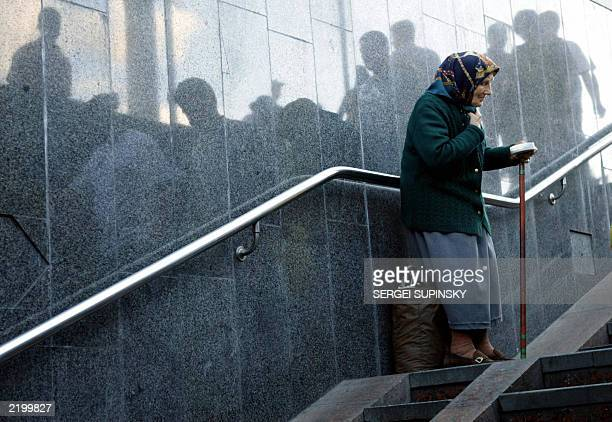 An old woman pensioner asks for alms at a Metro station in downtown Kiev 24 July while people reflected on the marble wall pass by her indifferently...