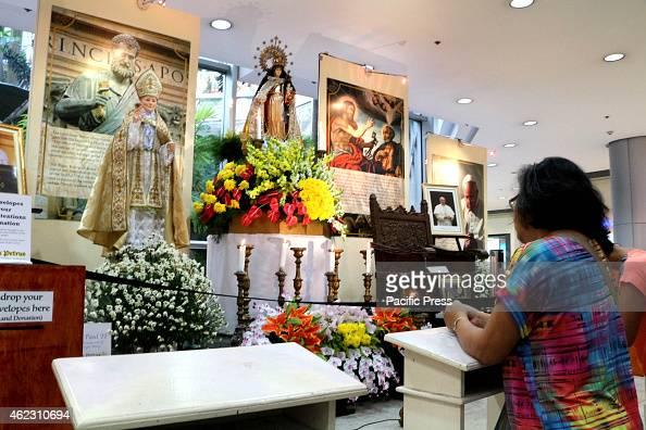 An Old Woman Praying At The Altar Of Virgin Mary And Saint John Paul