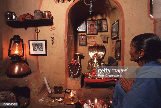 An old woman prays at an altar in her house during the Festival of the Snake For two days flowers are offered and prayers are said to live snakes in...