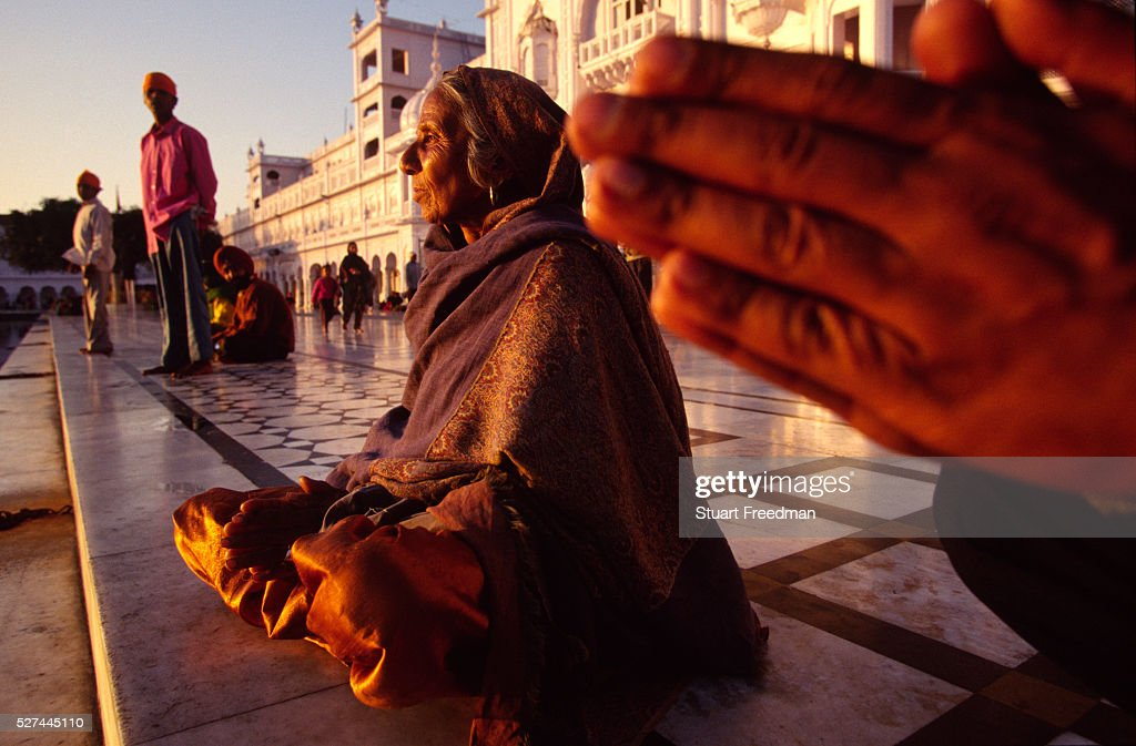 An old woman prays at the Golden Temple in the late afternoon sun The Golden Temple is also known as the Harmandir Temple and was built in 1574 It is.