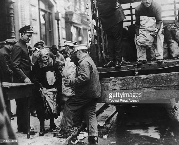 An old woman receives her Thanksgiving ration of food in New York during the Great Depression 7th November 1930 Tons of food were distributed...