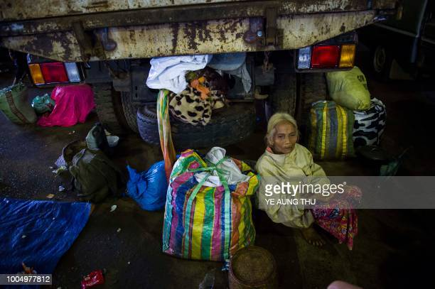 TOPSHOT An old woman rest with her belongings with other residents displaced by massive flood waters from the collapsed dam seek shelter in Paksong...
