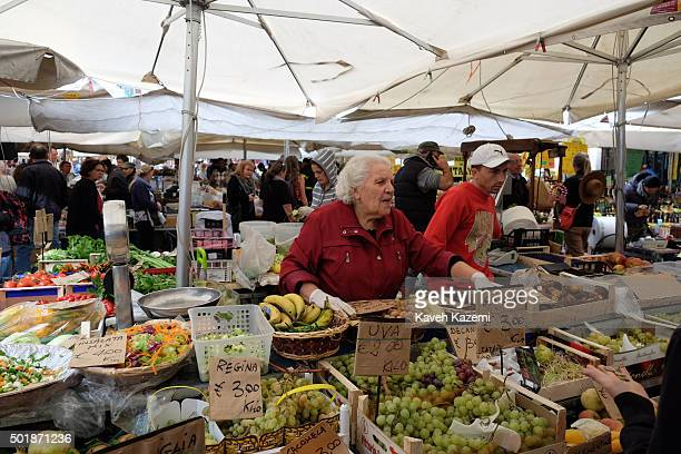 An old woman selling groceries seen in the Campo de Fiori day market on October 16 2015 in Rome Italy Campo de' Fiori is a rectangular square south...