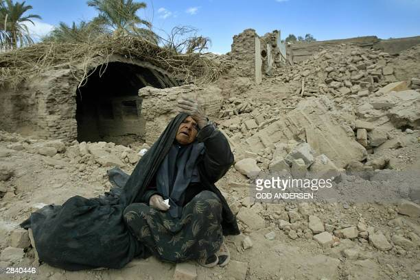 An old woman sits amid the rubble of her collapsed home in the earthquakestricken Iranian city of Bam 02 January 2004 US Senator Elizabeth Dole and a...