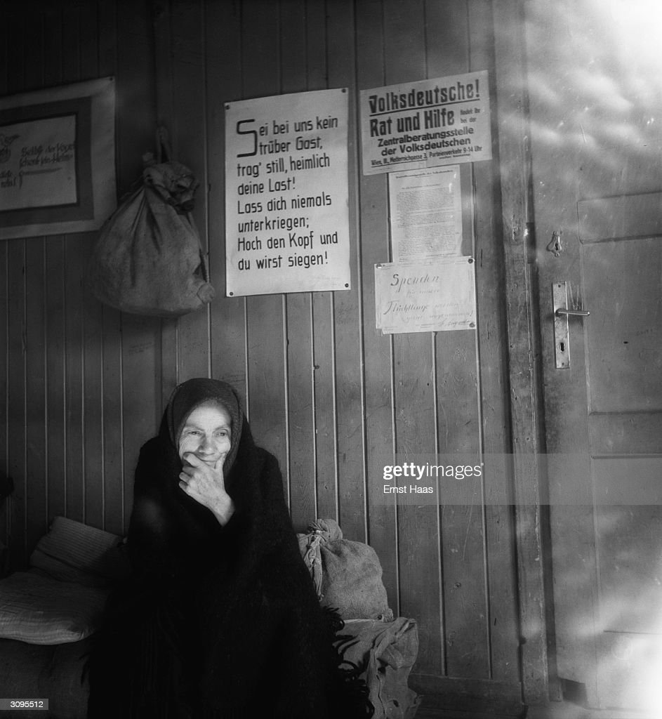 An old woman sits amidst her belongings in post-war Vienna. Above her a sign offers 'Advice and Assistance' ('Rat und Hilfe') to German people.