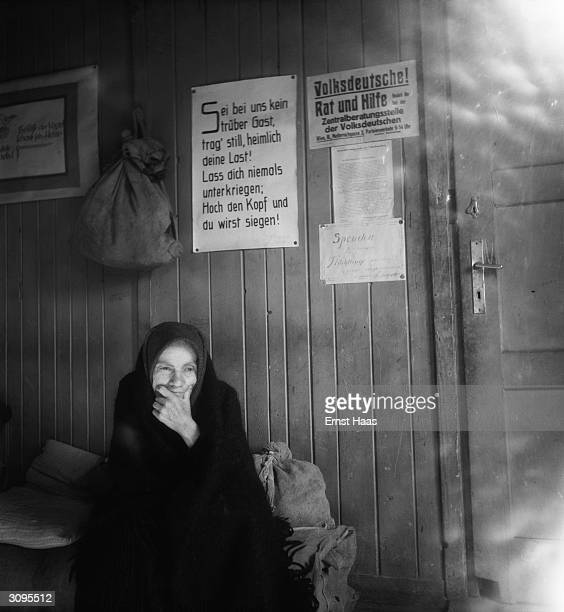 An old woman sits amidst her belongings in postwar Vienna Above her a sign offers 'Advice and Assistance' to German people